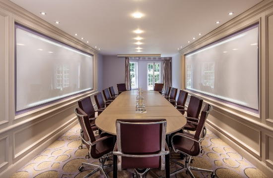 Large boardroom table with burgundy leather executive chairs and huge whiteboard on either side of the room