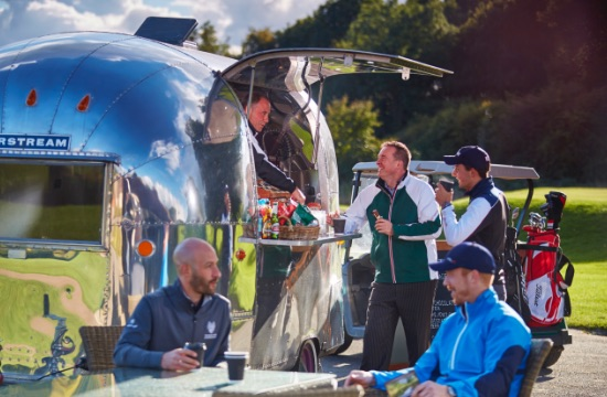 Golfers with golf buggy and golf clubs taking refreshments from an Airstream trailer operating as a mobile halfway hut on a golf course
