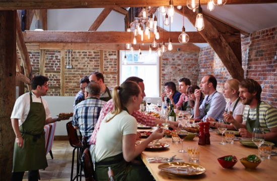 Mixed group on an incentive programme in a converted barn, wearing aprons and seated around a large farmhouse table whilst eating and talking