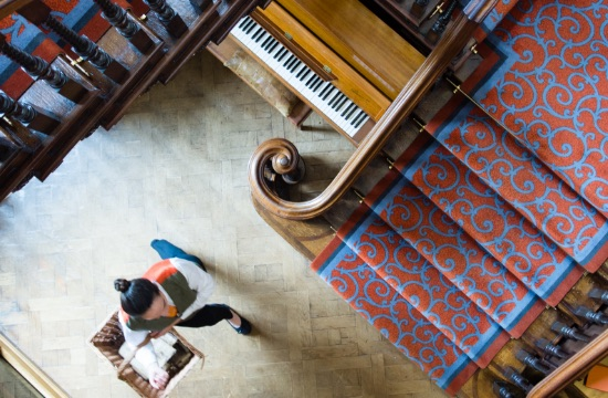 Ariel view of waitress carrying a wicker basket walking on parquet floors past a piano and sweeping staircase